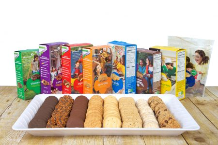 Alameda, CA - September 16, 2017: White tray with 8 varieties of Girl Scout Cookies on a wood table, boxes standing behind plate. Available annually during Girl Scout cookie sales